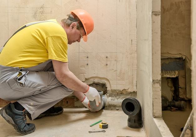 Trabalhador instalando um tubo de drenagem de esgoto para instalar o tanque embutido do banheiro