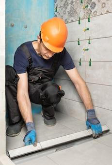 Trabalhador instalando uma tampa de ralo decorada com ladrilhos de cerâmica no banheiro