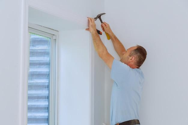 Trabalhador instalar guarnição em torno de uma janela