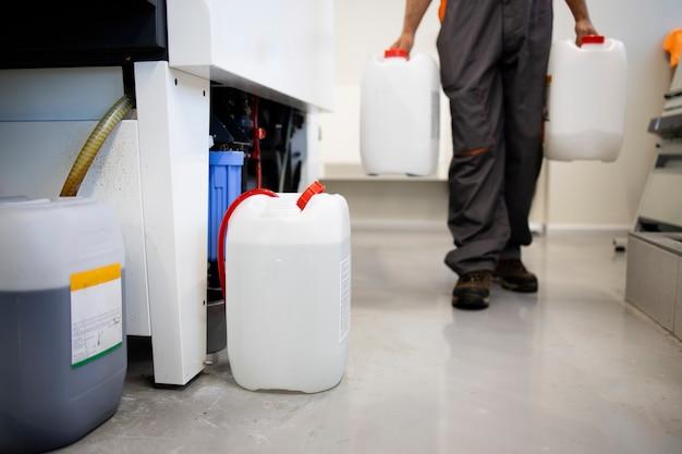 Trabalhador irreconhecível carregando garrafa com produtos químicos na fábrica.