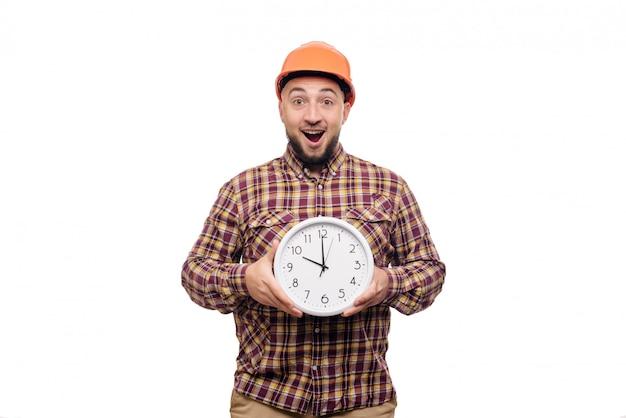 Trabalhador irritado do construtor no capacete alaranjado da construção protetora que mantém disponivel um despertador grande isolado no branco. hora de trabalhar. tempo de construção civil.