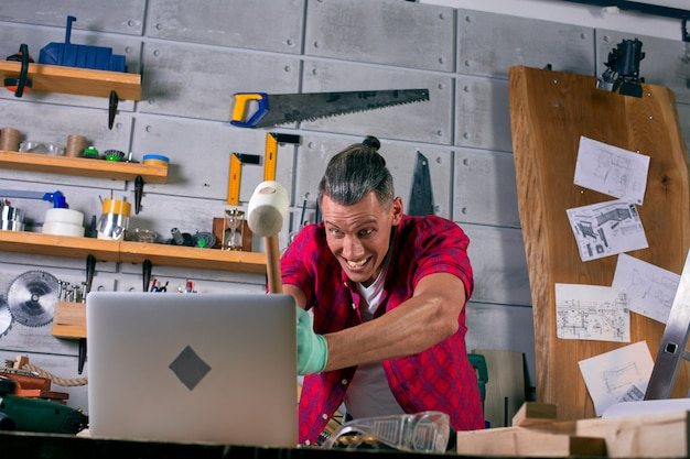 Trabalhador irritado na oficina bate um laptop com um martelo