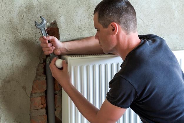Trabalhador jovem bonito encanador profissional instalar radiador de aquecimento na parede de tijolos, usando uma chave em uma sala vazia de um apartamento ou casa recém-construída.