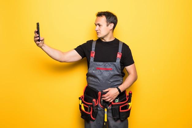 Trabalhador jovem com cinto de ferramentas, segurando o telefone