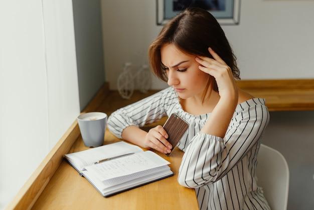 Trabalhador jovem garota freelancer sentado na loja de café com telefone, livro de nota