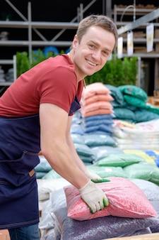 Trabalhador jovem na estufa do mercado de plantas no trabalho