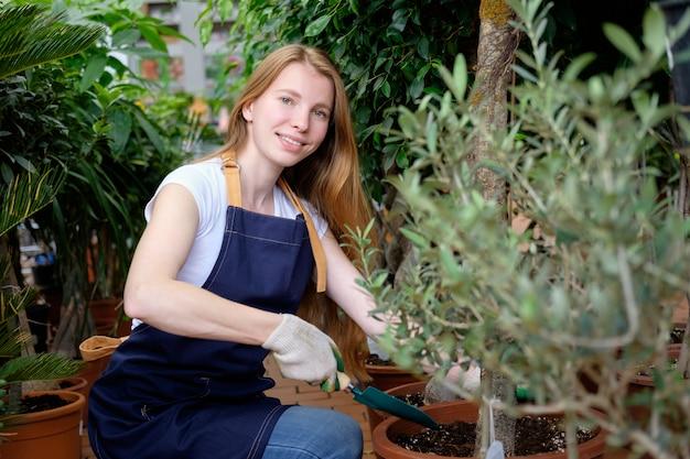 Trabalhador jovem ruiva na estufa do mercado de plantas capina plantas e sorrindo