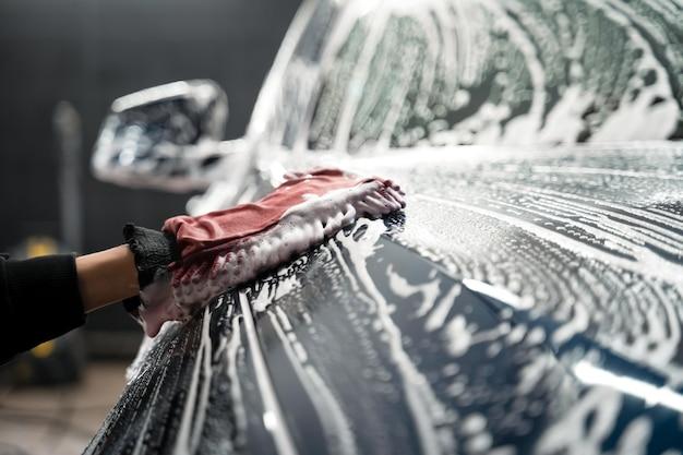 Trabalhador lava a carroceria do veículo com espuma e pano