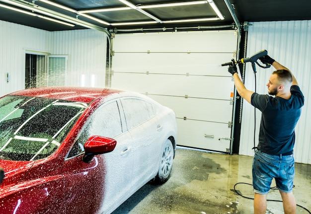 Trabalhador lavando carro com espuma ativa em uma lavagem de carro.