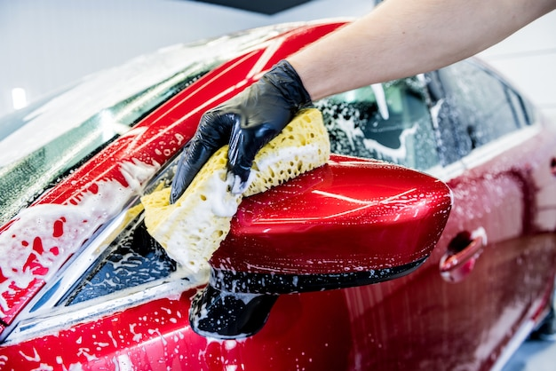 Trabalhador lavando carro vermelho com esponja em um lava-rápido