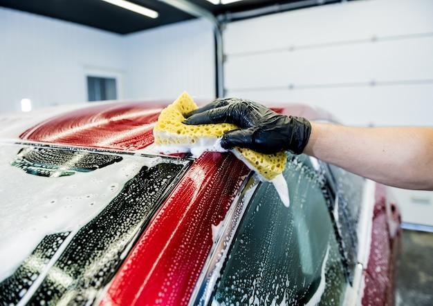 Trabalhador lavando carro vermelho com esponja em uma lavagem de carro.
