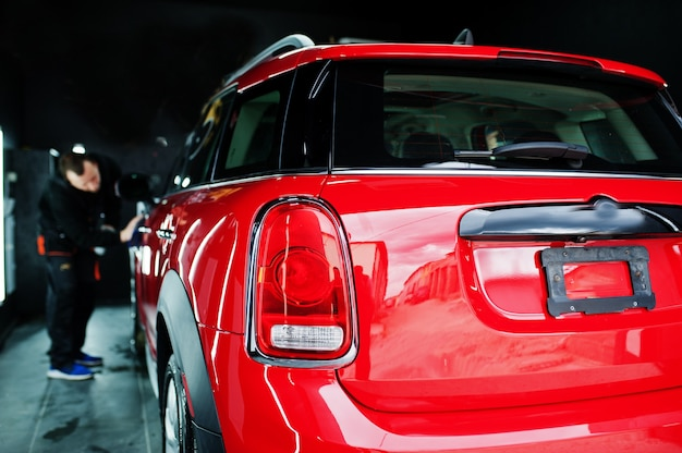 Trabalhador lavando carro vermelho na garagem de detalhamento