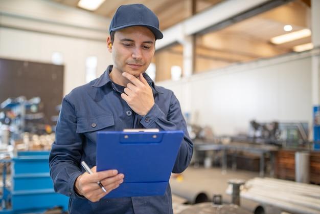 Trabalhador lendo um documento em uma grande instalação industrial