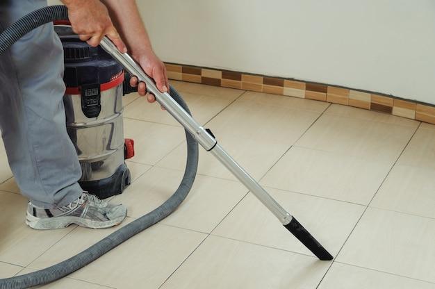Trabalhador limpa as costuras entre os ladrilhos usando um aspirador de pó