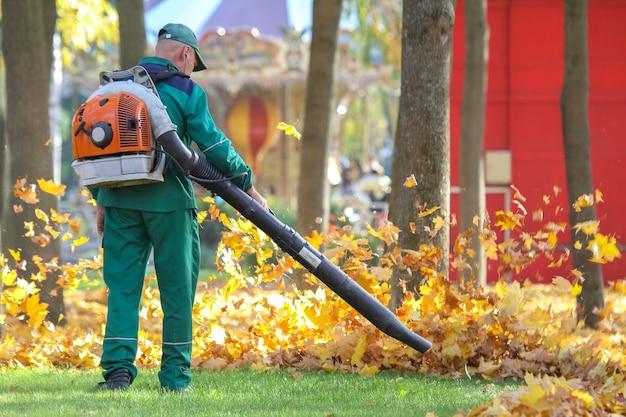 Trabalhador limpa folhas de outono com um ventoinha em um parque da cidade