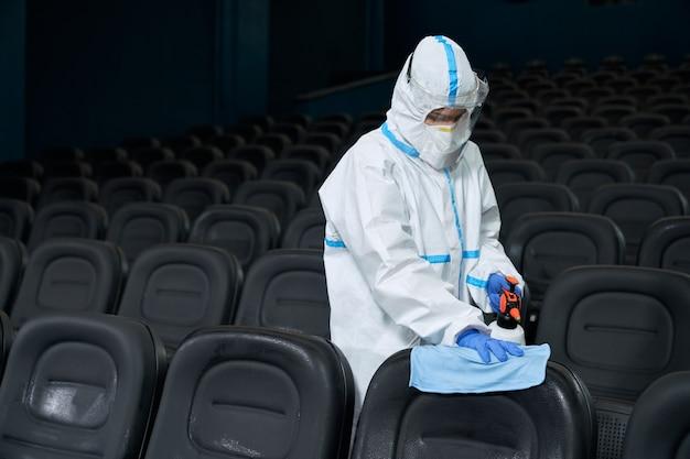 Trabalhador limpando cadeiras no cinema com pano