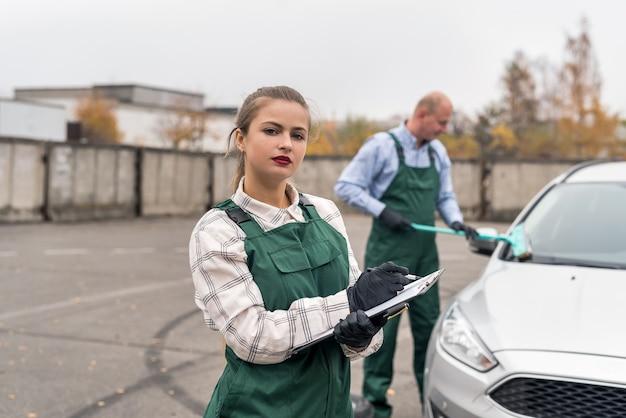 Trabalhador limpando carro e mulher com prancheta na estação de serviço