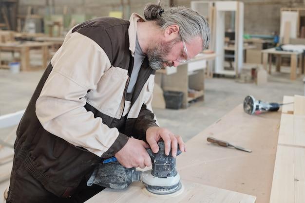 Trabalhador maduro da fábrica de móveis, curvado sobre a placa de madeira enquanto usa o moedor para alisar a superfície da peça de trabalho