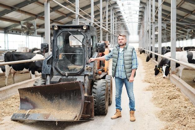 Trabalhador maduro e confiante em uma casa de fazenda moderna, parado ao lado de um trator ou outro equipamento de trabalho no longo corredor entre duas fileiras de vacas leiteiras
