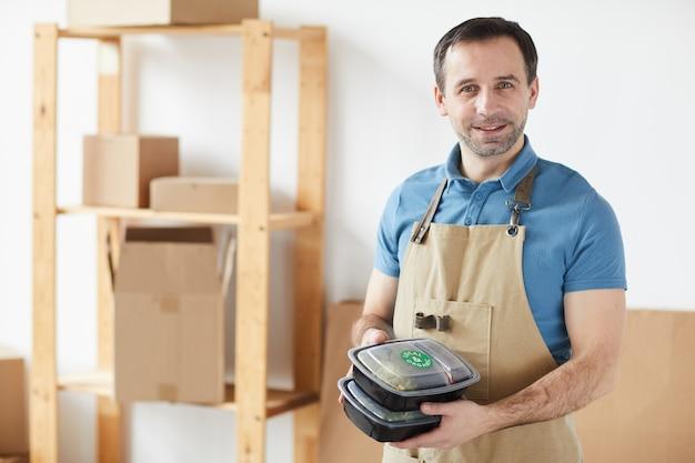 Trabalhador maduro vestindo avental e sorrindo enquanto segura pedidos de entrega de comida
