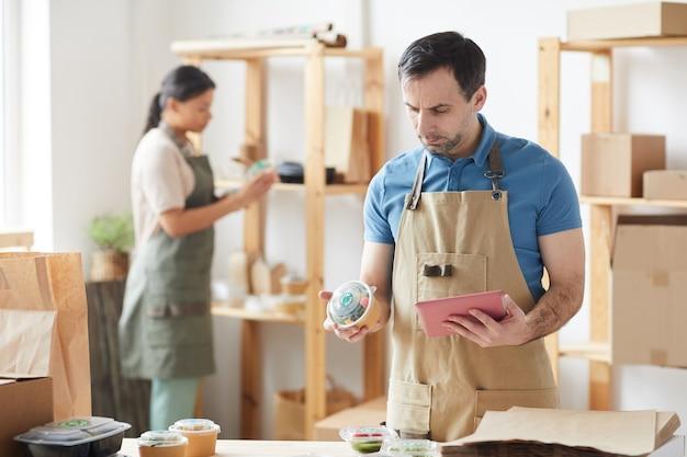 Trabalhador maduro vestindo avental encomendas de embalagem ao lado da mesa de madeira, serviço de entrega de comida