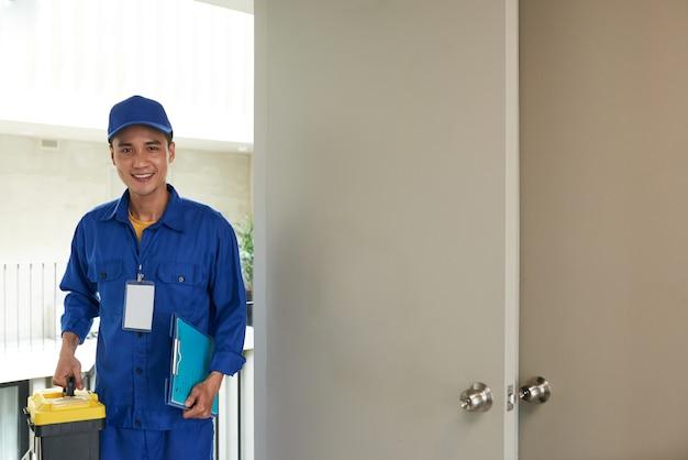 Trabalhador manual asiático alegre que chega na chamada de casa