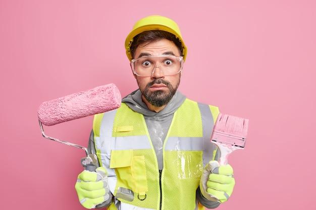 Trabalhador manual barbudo atordoado segura rolo de pintura e pincel, usa ferramentas especiais envolvidas na construção e no conserto, usa capacete de proteção e uniforme
