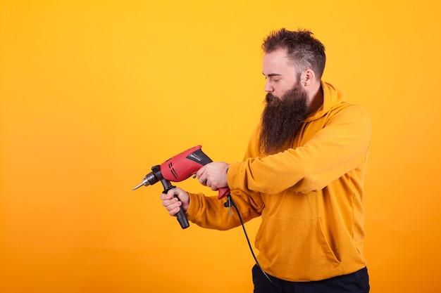 Trabalhador manual barbudo com capuz amarelo segurando a furadeira sobre fundo amarelo. trabalhador. furadeira. trabalho masculino.