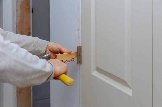 Trabalhador manual carpinteiro instalação na porta de madeira interior com martelo