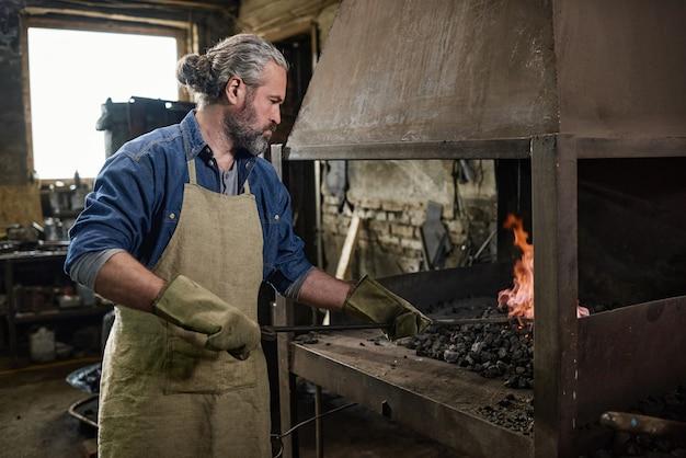 Trabalhador manual colocando o carvão na fornalha e queimando o fogo na oficina
