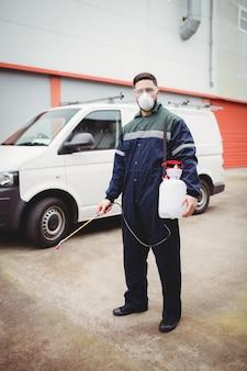 Trabalhador manual com inseticida em pé na frente de sua van