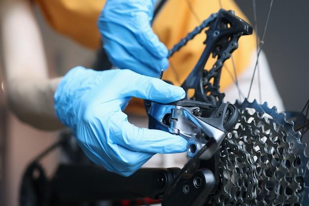 Trabalhador manual com luvas de borracha consertando bicicleta na oficina