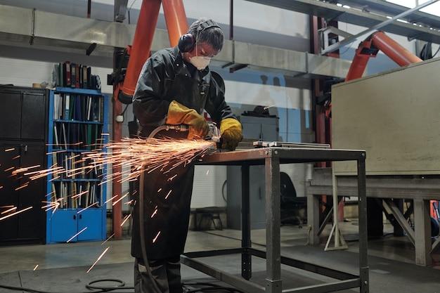Trabalhador manual com máscara e protetores de ouvido em pé em uma mesa alta de metal e cortando metal com ferramenta rotativa em loja industrial