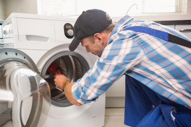 Trabalhador manual consertando uma máquina de lavar roupa