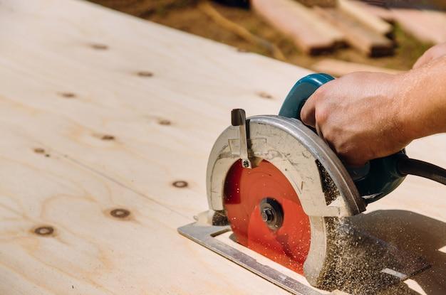 Trabalhador manual cortar madeira compensada na serra circular