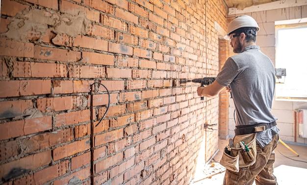 Trabalhador manual em um canteiro de obras no processo de perfuração de uma parede com um perfurador.