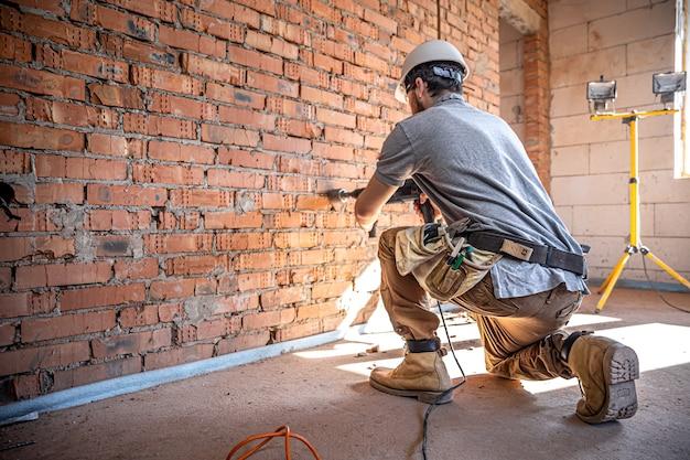 Trabalhador manual em um canteiro de obras no processo de perfuração de uma parede com um perfurador
