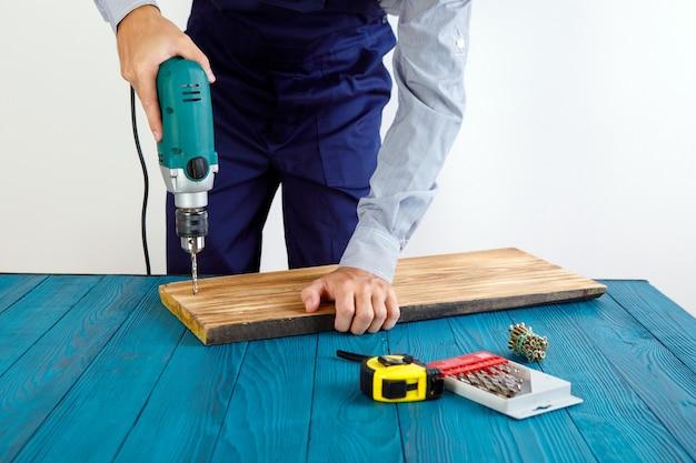 Trabalhador manual em uniforme azul funciona com chave de fenda elétrica automática. concepção de renovação de casa.