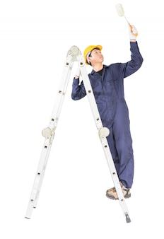Trabalhador manual, em, uniforme, ficar, escada, enquanto, usando, rolo pintura, com, caminho cortante