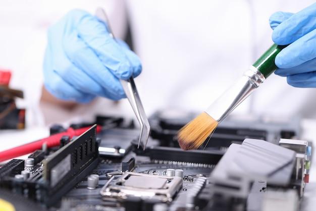 Trabalhador manual enluvado com escova e pinças repara a placa-mãe. manutenção de equipamentos de informática
