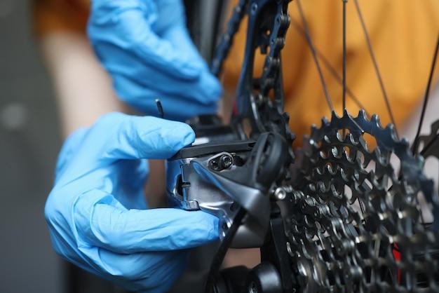 Trabalhador manual enluvado conserta cassete traseiro de bicicleta