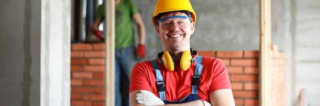 Trabalhador manual feliz no retrato uniforme