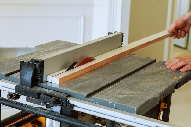 Trabalhador manual irreconhecível cortador de serra circular de madeira na casa nova