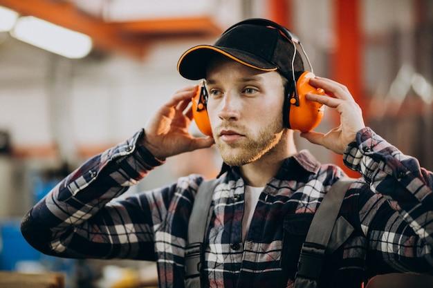 Trabalhador manual masculino novo com fones de ouvido de segurança
