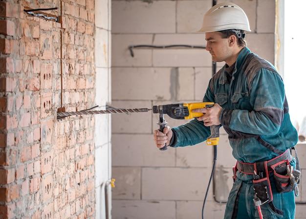 Trabalhador manual no processo de perfuração de uma parede com um perfurador.