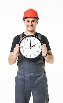 Trabalhador manual novo preocupado com o tempo no fundo branco