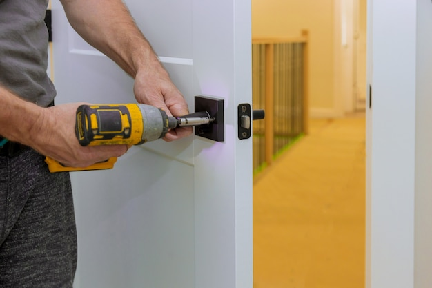 Trabalhador manual que instala a fechadura da porta na sala com chave de fenda