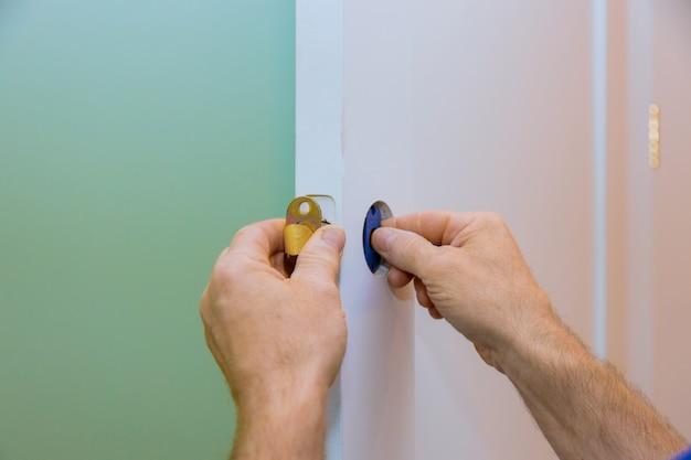 Trabalhador manual que instala a fechadura da porta nas mãos do trabalhador, instalando o novo cacifo da porta