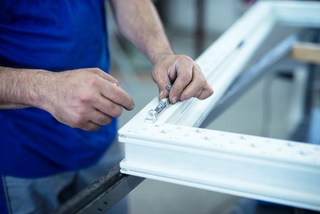 Trabalhador manual que monta dobradiças em portas e janelas de pvc.