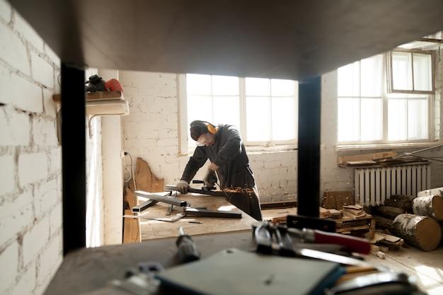 Trabalhador manual que motiva objetos metálicos de aço em oficina com ferramentas